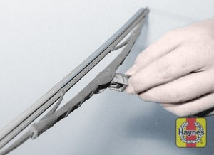 Illustration of step:  To remove the rear wiper blade, tilt the wiper blade, depress the retaining tab and slide the blade out of the hooked end of the arm, taking care not to allow the arm to spring back and damage the rear screen - step 4