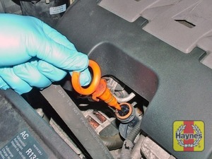 Illustration of step:  The dipstick is located at the front of the engine (see Underbonnet check points); the dipstick is often brightly coloured or has a picture of an oil-can on the top for identification - Car care - step 11