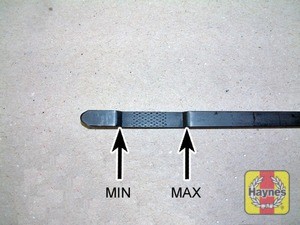 Illustration of step:  Note the oil level on the end of the dipstick; it should be in the cross-hatched area - never above the 'MAX' line or below the 'MIN' line - Vehicle care - step 11