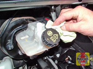 Illustration of step:  If topping-up is necessary, first wipe clean the area around the filler cap to prevent dirt entering the hydraulic system -  	 		Safety first 	! - step 29