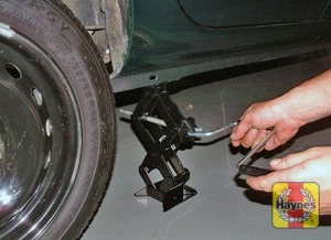 Illustration of step:  Locate the jack below the reinforced point on the sill (don't jack the vehicle at any other point of the sill) and on firm ground, then turn the jack handle clockwise until the wheel is raised clear of the ground - step 7
