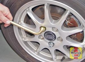 Illustration of step:  Slacken each wheel bolt by a half turn, using the wheel brace - step 4