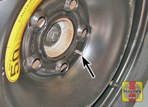 Illustration of step:  Fit the spare wheel, noting that there is a special locating peg (arrowed) on the wheel hub, which must fit through the hole in the temporary spare wheel, or into the space inside the wheel hub on regular roadwheels - step 8