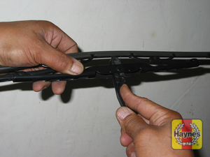 Illustration of step:  4 Press on the release tab and push the blade assembly down out of the hook in the arm  - step 4