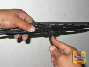 Illustration of step:  6 Lift the arm assembly away from the glass for clearance, press on the release lever, then slide the wiper blade assembly out of the hook in the end of the arm  - step 6