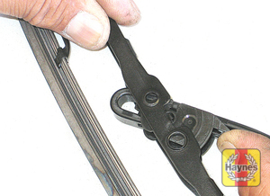 Illustration of step: 6 Press in on the tab and push the blade assembly out of the hook at the end to remove it  - step 6