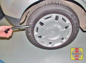 Illustration of step:  Prise off the wheel trim (or alloy wheel centre cover) from the punctured wheel, using the end of the wheelbrace - step 5