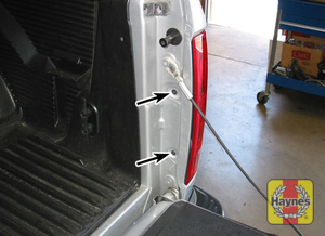 Illustration of step:  1a To detach the taillight housing from the rear fender, open the tailgate and remove these two mounting screws  - step 1
