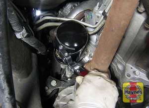 Illustration of step: Using an oil filter wrench, unscrew the filter counterclockwise and remove the old oil filter - step 3