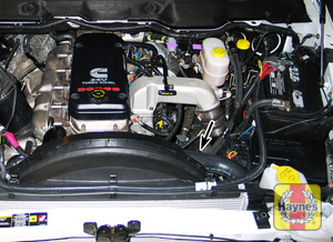 Illustration of step: The power steering fluid reservoir is located in the engine compartment - step 1
