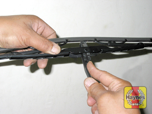 Illustration of step:  5 Lift the arm assembly away from the glass for clearance, press on the release lever, then slide the wiper blade assembly out of the hook in the end of the arm  - step 5
