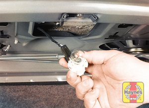 Illustration of step: 1 To replace a back-up light bulb on a Chevrolet model (located in the trunk lid), turn the bulb socket counterclockwise and detach it from the lens housing, pull it down and remove the bulb from the socket - step 1